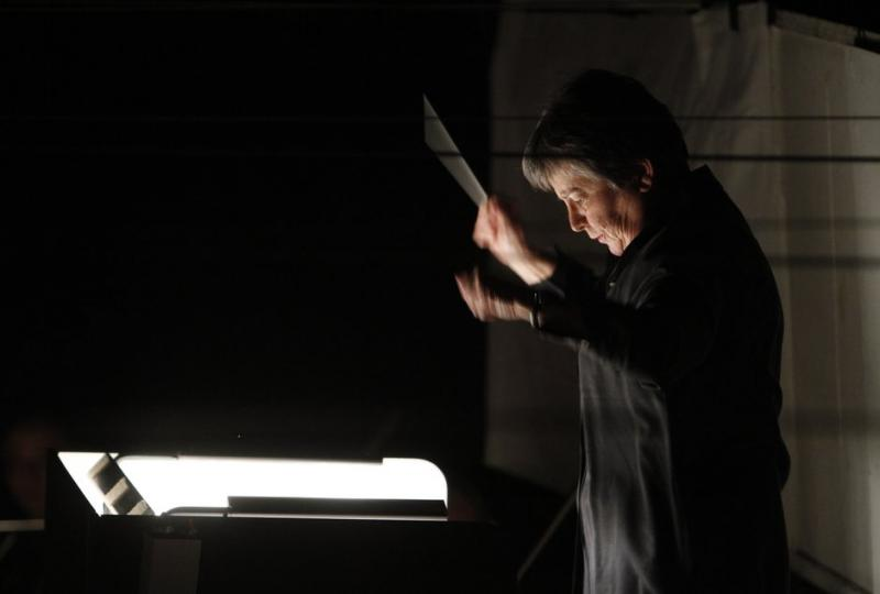 In a darkened theatre, Karen Keltner conducts the orchestra. She is looking down at her musical score which is spread out on a stand.