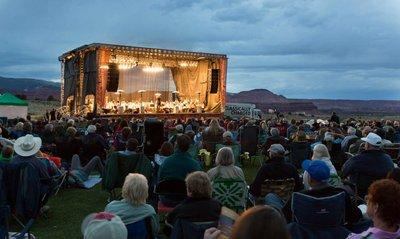 The audience sits outside on the grass to hear the Utah Symphony play, with gorgeous southern utah scenery in the background.