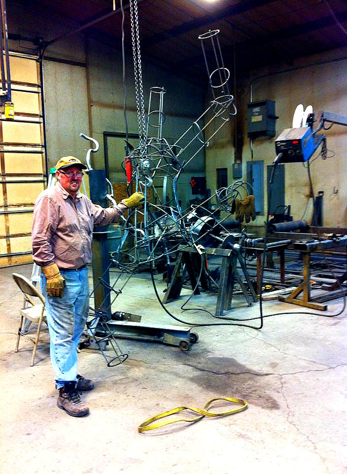 The artist, Cache Valley local Michael Bingham, in his studio with the skeleton of his enormous, floating astronaut sculpture.