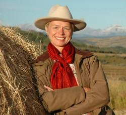 A woman with a cowboy hat, tan jacket, and bright red scarf leans against a hay bale.