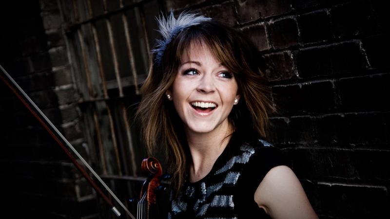 Side view of Lindsey Stiling, with violin in hand and a feather in her hair. Leaning up against a brick wall.