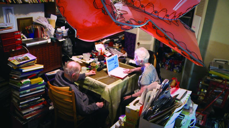 The elderly couple in their living room, which is teeming with artwork.
