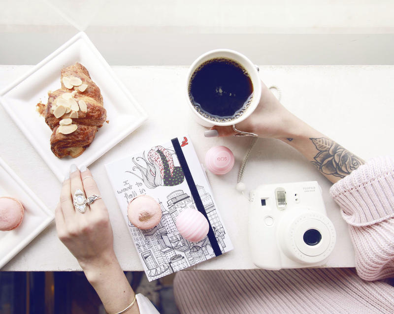 A photograph showing someone with a coffee, notebook, and assorted pastries.
