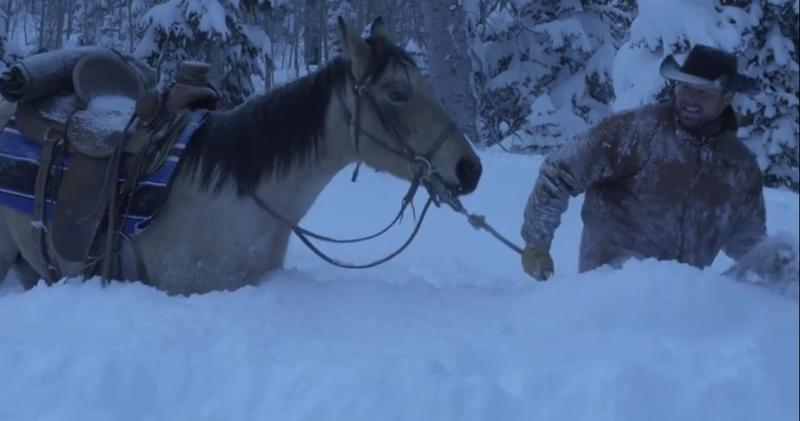 Man is hip-deep in snow, attempting to traverse a mountain with his horse.
