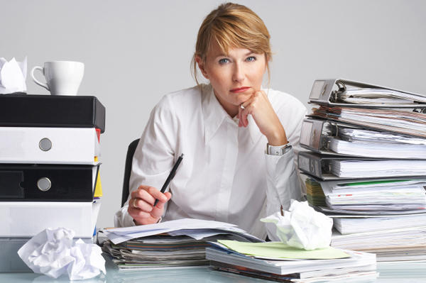 Woman looking stressed with piles of books, crumpled papers, and cups of coffee.