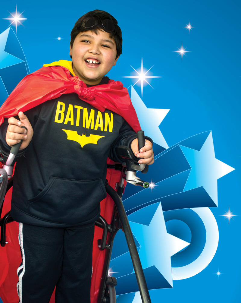 A child with a walker dressed in a Batman costume on a blue background with stars.