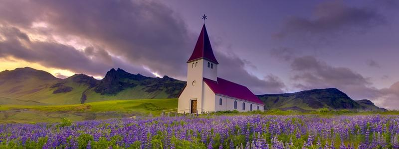 A quaint, little church in the middle of an expansive field.