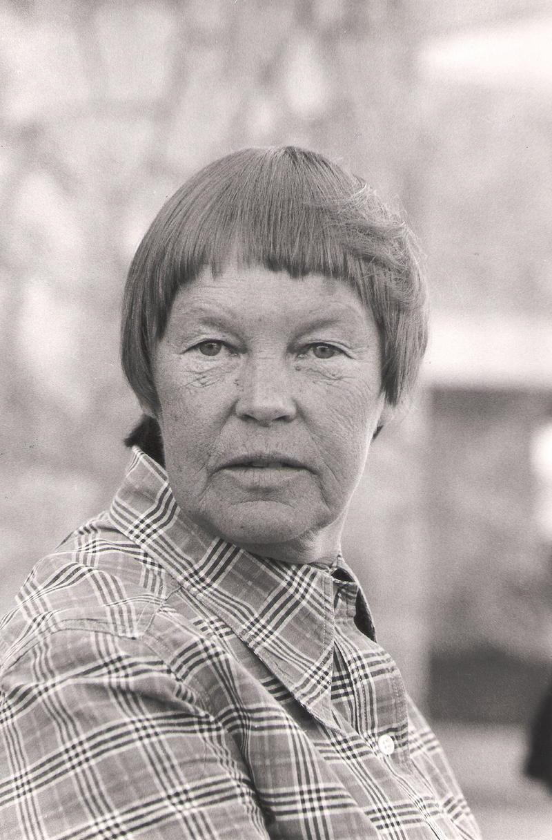 May Swenson, a woman with a short haircut and plaid shirt, looks directly at the camera.