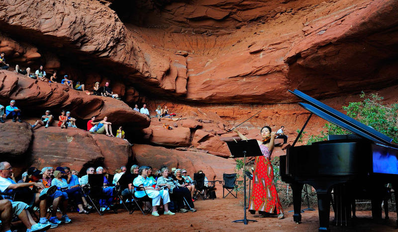 Surrounded by a red rock formation, guests listen to a pianist and violinist in concert.