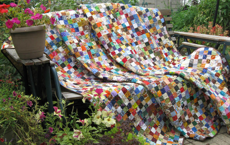 A quilt draped across a bench outside, with potted plants