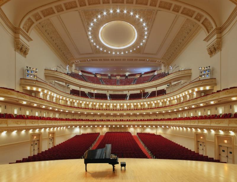 A grand piano on the stage at Carnegie Hall, looking out into the audience.