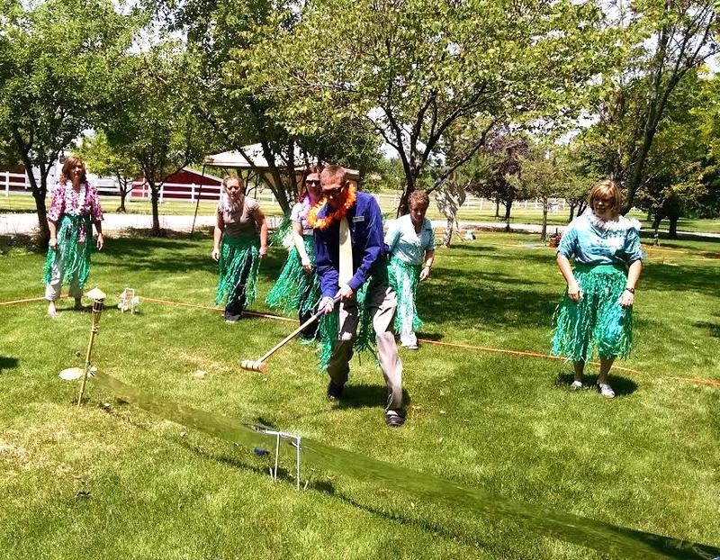 A croquet team, dressed in grass skirts and leis, competes in a dry run of the croquet tournament