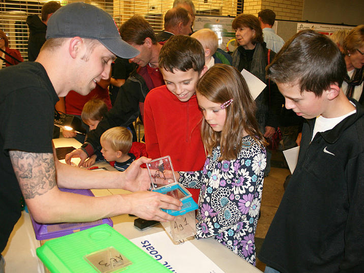 Kids gather around an activity station after the lecture to get 'hands on' with science.