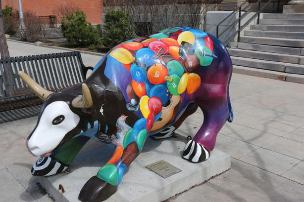 A bull statue covered in M&M's painted by various Cache Valley High Schools