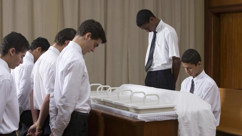 The Mormon Priesthood serving sacrament, including colored patrons.