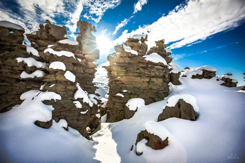 Sunlight peeking between rocky craigs, reflecting off the Unita Mountain snow pack.