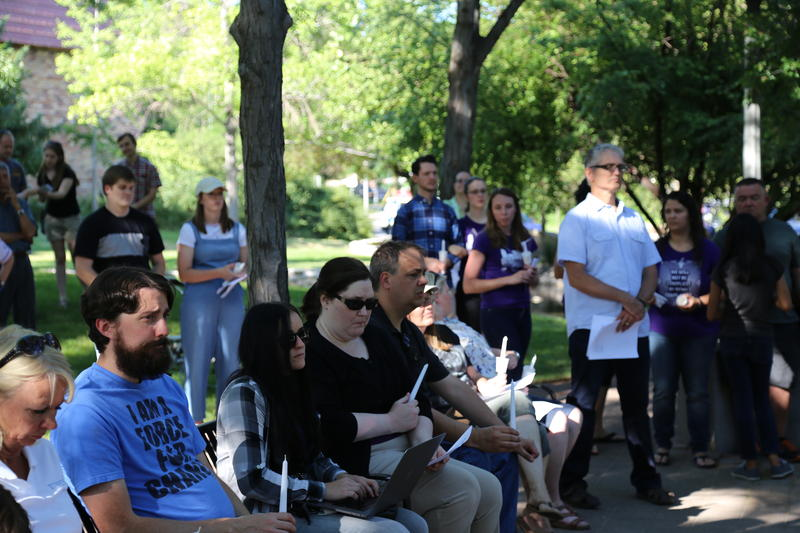 Seated attendees listen to speakers at the vigil holding unlit candles.