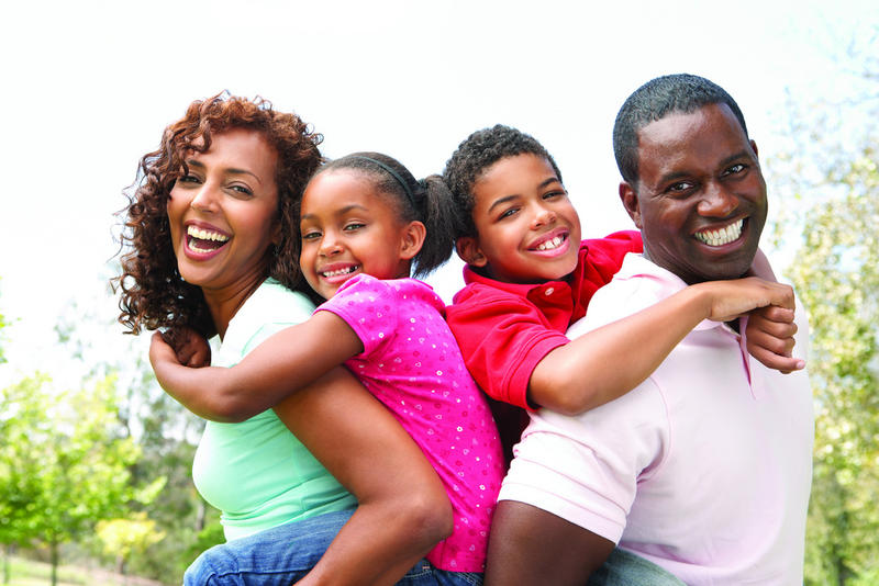 Black American family, smiling together; Black households tend to fare worse economically despite overall prosperity in Utah
