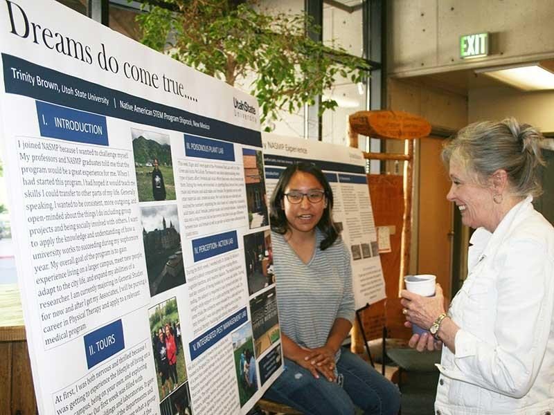 A Native American scholar presents her research to the Science college dean at Utah State University. White poster with photos and descriptive text about the student's research.