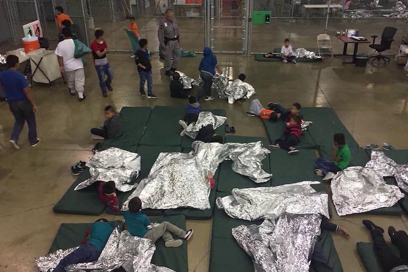 Group of migrant children together on mats with silver shock blankets.