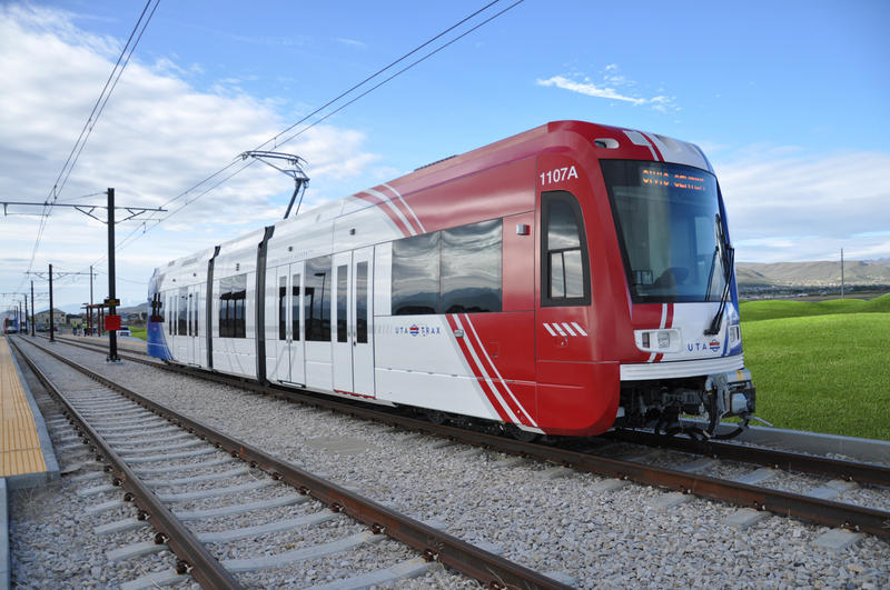 A TRAX light rail train pulls into the station with railroads, green grass, and a blue sky.