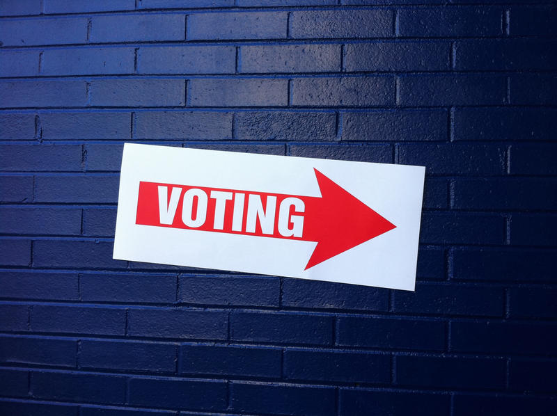 Sign that says Voting with an arrow hanging on blue brick wall