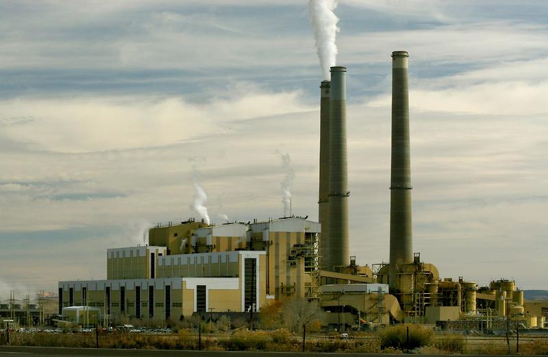 Three smokestacks and coal plant building beneath partly cloudy sky