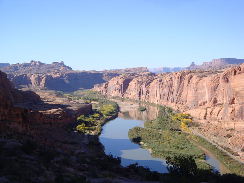 Blue sky and red desert cliffs above a curved portion of river.