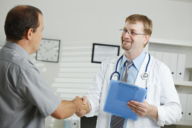 White middle-aged male doctor greets white middle-aged male patient. They shake hands.