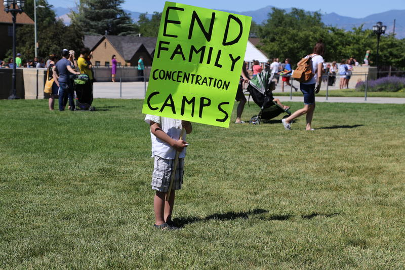 "Standing on a field of grass a child holds a sign that says ""End family concentration camps."" The child's face is hidden by the sign."