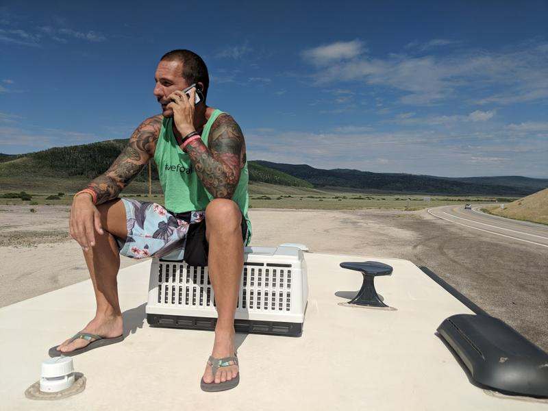 Sitting atop his RV near Fruitland, Utah runner Christian Griffith does a telephone interview with Utah Public Radio's Kerry Bringhurst