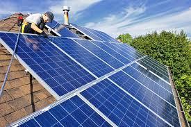 Man installs home solar panels.