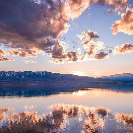 Pink and blue clouds float over Utah Lake with the mountains in the background.