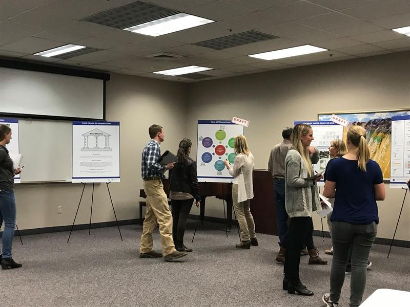 People at an open house in front of posters: The Utah Division of Water Resources held an open house in Logan Tuesday night — one of many that have been held all over the state.