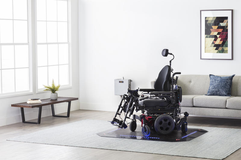 Electric wheelchair sits on a black pad in a white living room with a table, painting, and sofa.