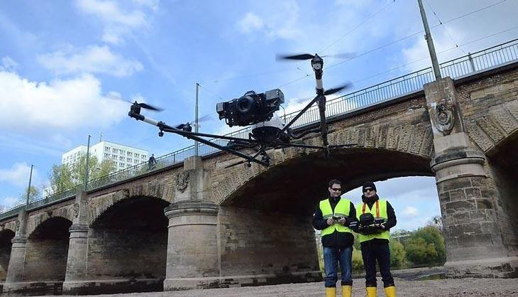 Background blue sky and white clouds. Middle stone bridge. Foreground two men in yellow jackets control a drone seeing in the middle.