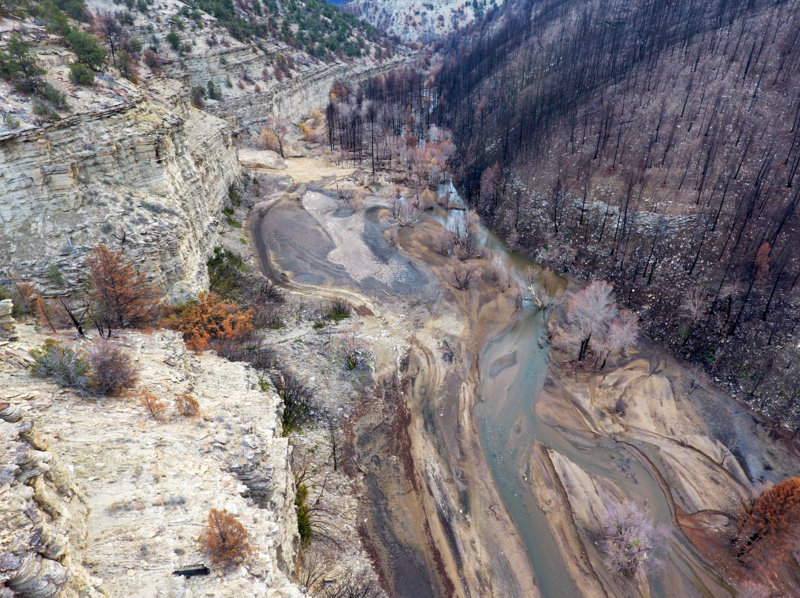 Top right is a charred slope with burned trees, middle is a deep canyon where the river has been dramatically altered, left side is an unburned slope.