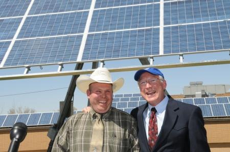 Andy Swapp (left) with Secretary Ken Salazar in front of a newly installed solar panel at Milford High School.