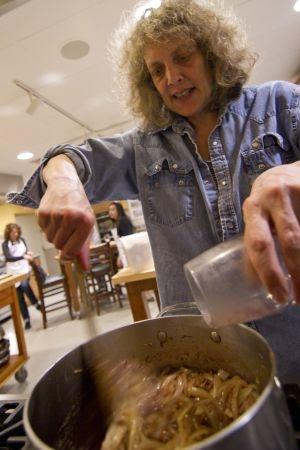 Sally Pollak stir in some red wine to the pot filled with chopped onions for a french soup
