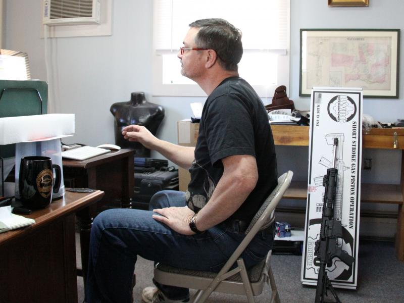 Gun store owner Henry Parro posts an ad for a gun on his store's Website on Monday in Waterbury. Parro says his store has seen a