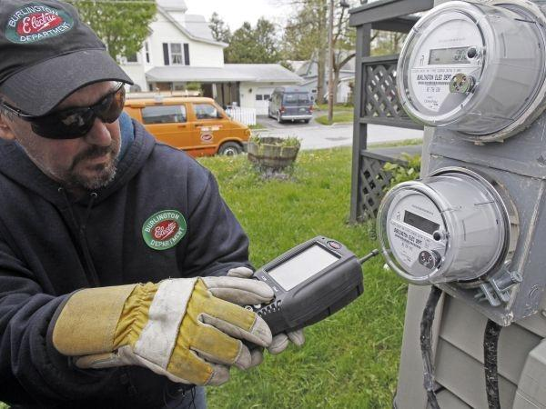 "Mark Delbeck of Burlington Electric, checks the radio frequency of a newly-installed ""smart"" meter on Thursday, May 10, 2012 in"