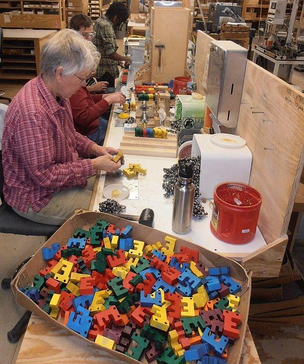Workers at Maple Landmark prepares alphabet train cars.