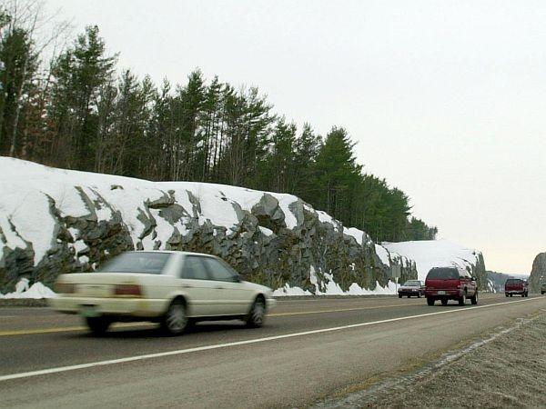 Cars driving on a highway with tree and snows in the background.
