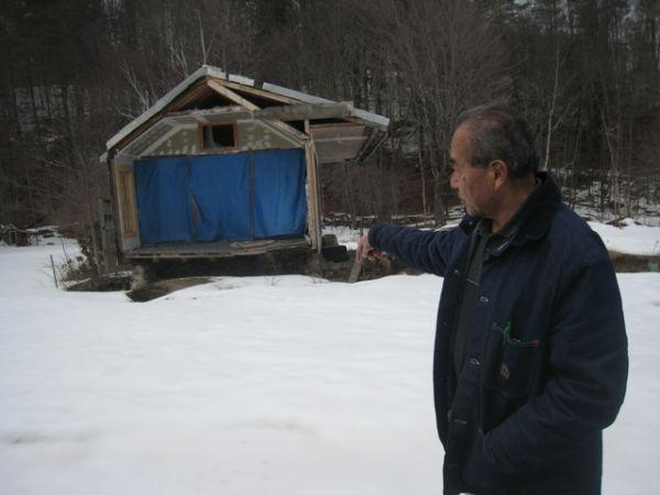 Dave Kaneshiro of Jamaica points to what's left of his house, which was destroyed by Tropical Storm Irene. He and three other