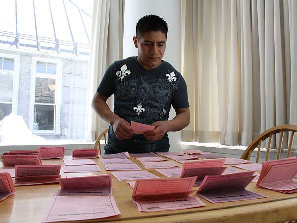 Patricio Antonio Hernandez, who works on a dairy farm in Richmond, organizes stacks of messages in support of the drivers' authorization bill in the Statehouse cafeteria on Monday.