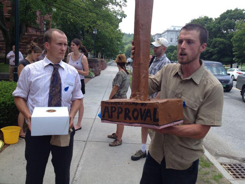 Anti-pipeline protesters brought a giant rubber stamp to present to officials at Department of Public Service, symbolizing the state's support of the natural gas pipeline. Officials did not take the stamp, but did accept a box of pastries and a written st