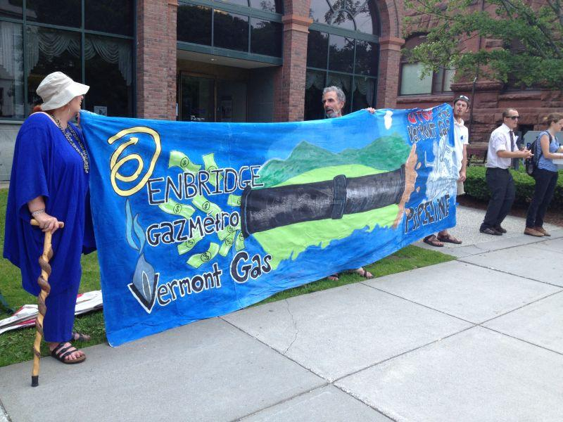 A banner at the pipeline protest points to shared ownership between the energy companies that want to develop the natural gas line as well as an oil pipeline that could be converted to ship tar sands through northern Vermont