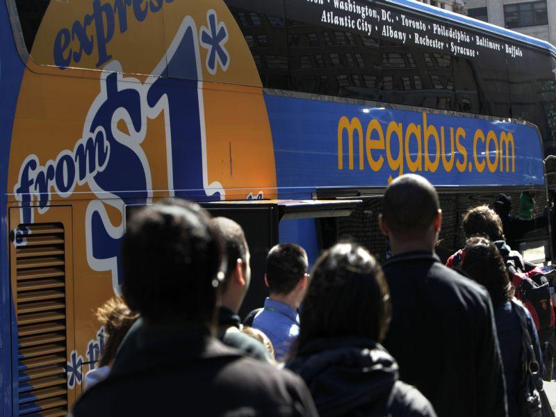 Passengers wait in line to board a Megabus in New York, Thursday, March 17, 2011. The past few years have seen exhilarating expansion of bus service in the Northeast.