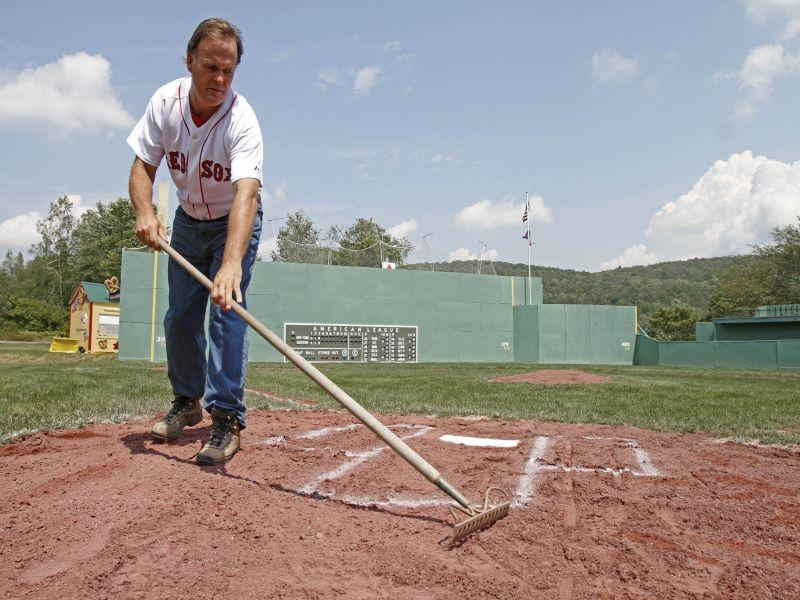 Pat O'Connor rakes around home plate at Little Fenway, a scaled-down version of the major league field in Essex, Vermont