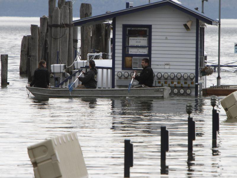 In this April 29, 2011 photo, workers at the Lake Champlain ferry dock paddle through the flooded parking lot in Burlington, Vt.
